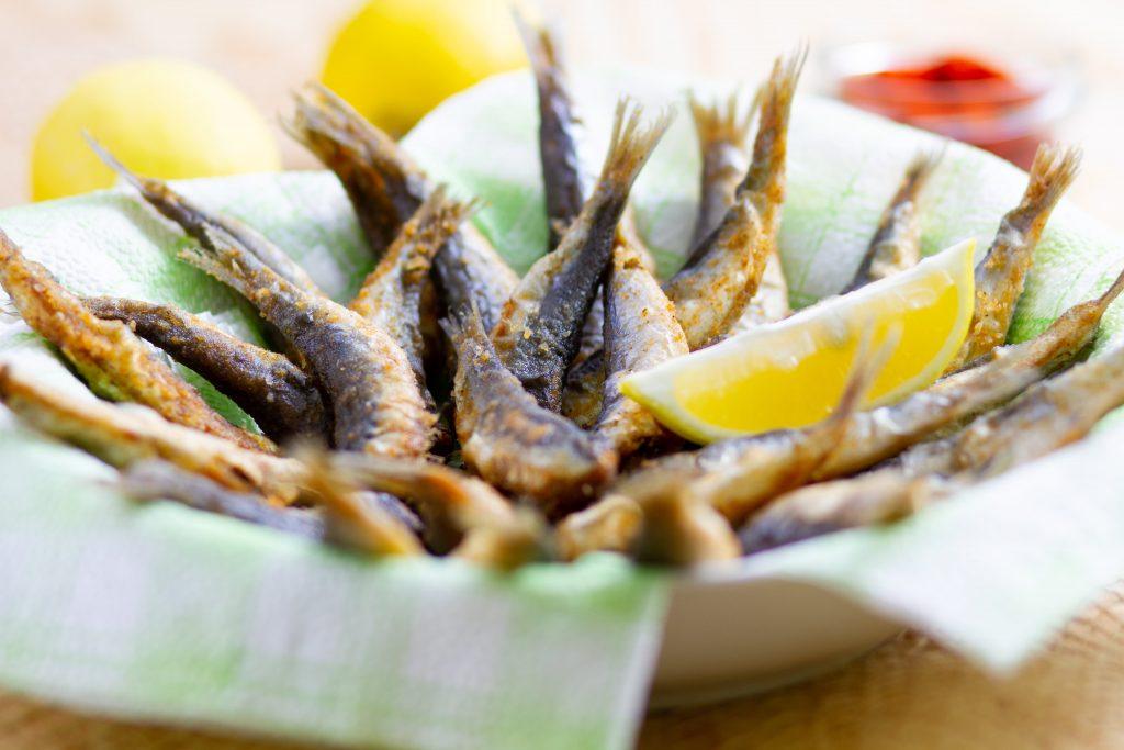 Deep-fried sardines served with lemon